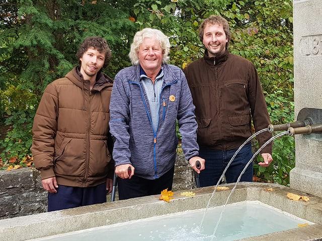 Drei Männer vor einem Brunnen.