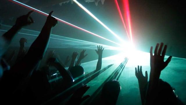 Leute in der Disco halten ihre Hände in die Höhe.