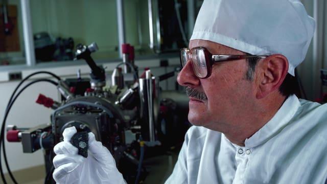 Ein Forscher schaut ein Stück des Meteroiten genau an.