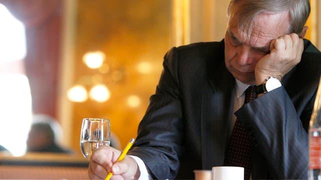 Alexander Pereira sitzt in sich gekehrt an einem Tisch, die eine Hand stützt seinen Kopf.