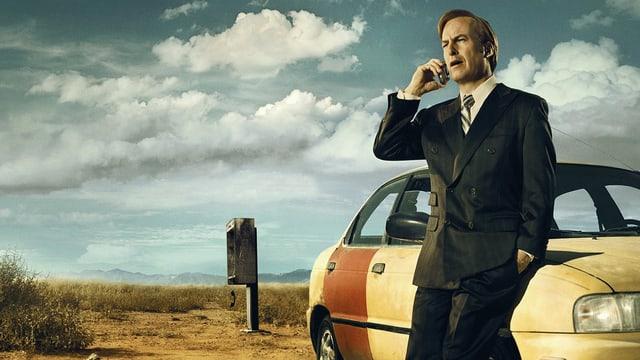Ein Mann steht in der dürren Landschaft, lehnt sich an sein Auto und telefoniert.