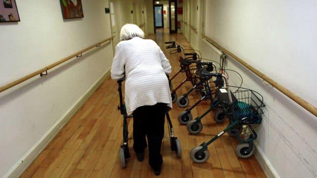 Eine Bewonerin eines Altersheim geht am Rollator durch einen Gang ihres Altersheimes