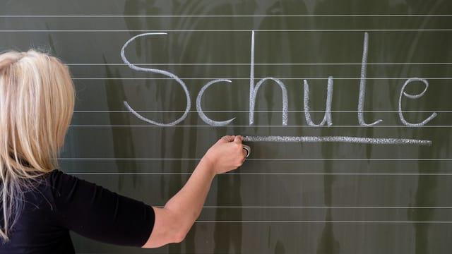 Eine Frau schreibt Schule an die Wandtafel