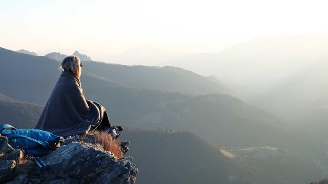 Eine Frau sitzt auf einem Berg. Sie ist in eine Decke eingehüllt.