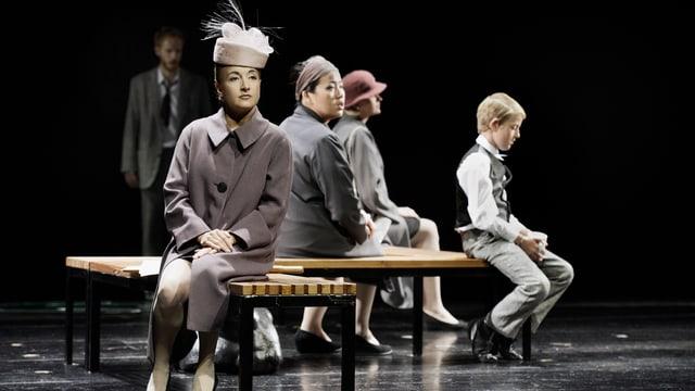 Drei Frauen mit Hüten und ein kleiner Junge sitzen auf Bänken.