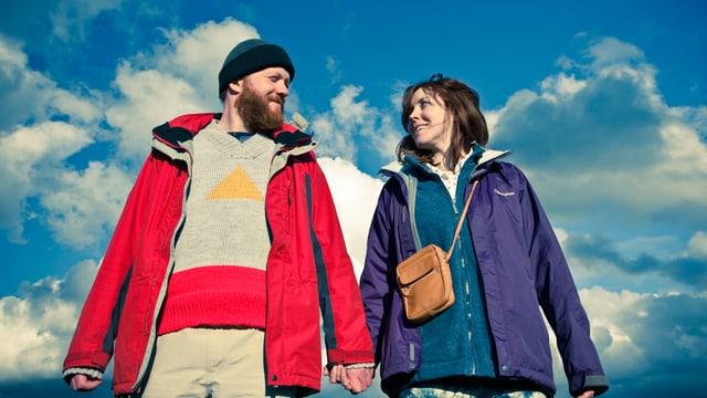 Mann und Frau unter blauem Himmel mit Quellwolken.