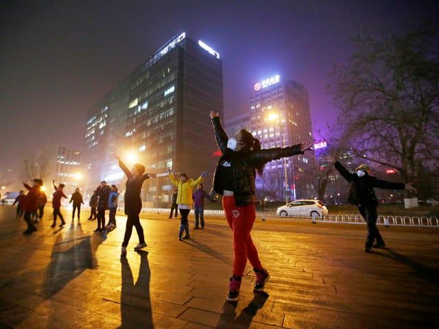 Tanzende Frauen auf einem Platz bei Nacht