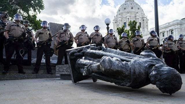 Polizisten stehen hinter der umgestossenen Statue