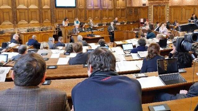 Grossratssaal. Man sieht viele Parlamentarierinnen und Parlamentarier von hinten. Vorne spricht Patrick Hafner von der SVPam Rednerpult.