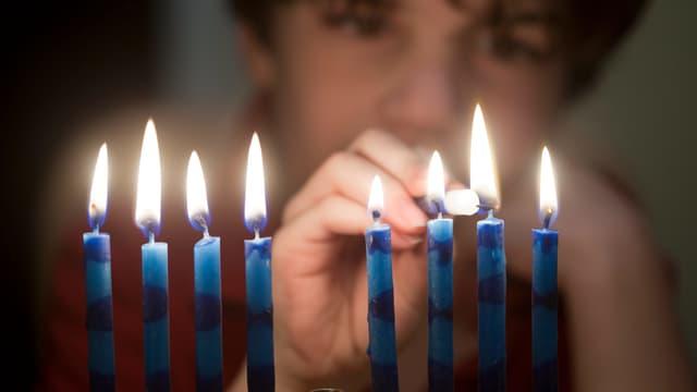 Ein Junge zündet die Kerzen der Menora an.