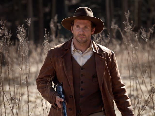 Bradley Cooper mit Hut und einem Gewehr.