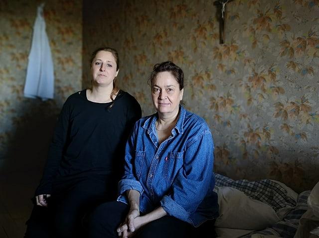 Zwei Frauen sitzen auf einem Bett.