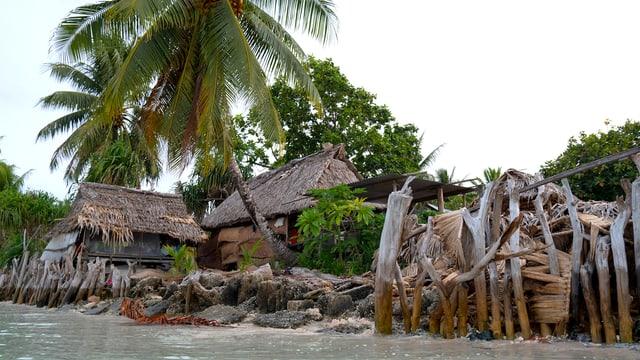 Blick vom Wasser auf einfache Hütten.