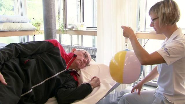 Ein Patient liegt auf einer Liege, die Therapeutin sitzt vor ihm mit einem bunten Ball.