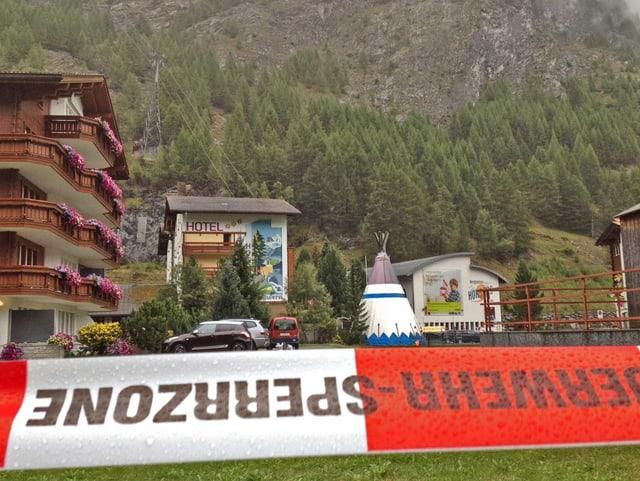 Absperrband der Feuerwehr und Talstation der Bergbahn.