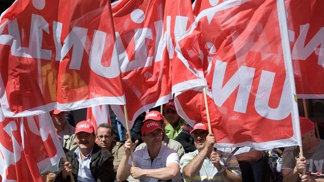 Männer mit rot-weissen Unia-Fahnen, die im Wind wehen.
