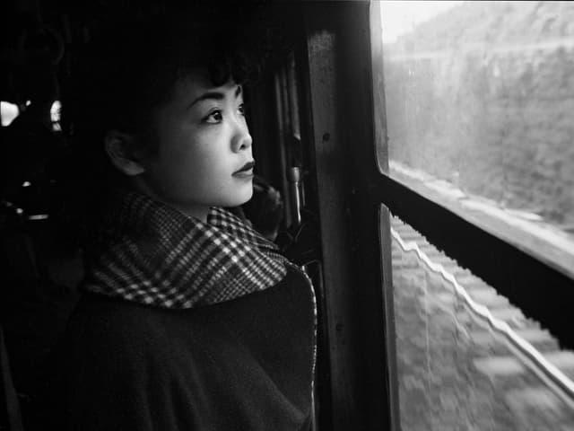 Frau sieht aus dem Zugfenster.