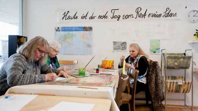Drei Frauen sitzen an einem Tisch und malen.