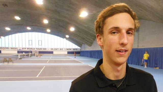 Portraitbild von Dennis Dambach; er steht in der Tennishalle «Paradies» von Roger Brennwald.