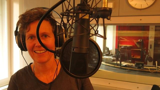 Katrin Ginggen mit Kopfhörer vor einem Mikrofon im Studio