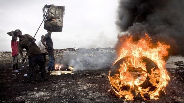 Vier junge Kinder wühlen im Schrott. Im Vordergrund steht ein alter Autoreifen in Flammen und stösst giftigen Rauch aus.