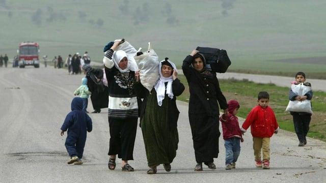 Eine Flüchtlingsfamilie mit Gepäck auf der Landstrasse.