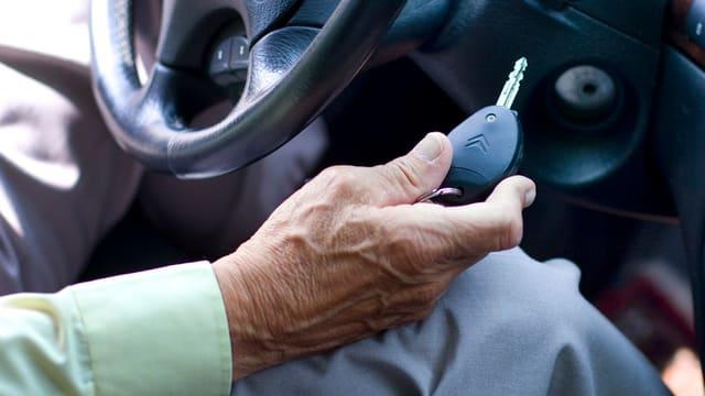 Hand einer alten Person hält Autoschlüssel