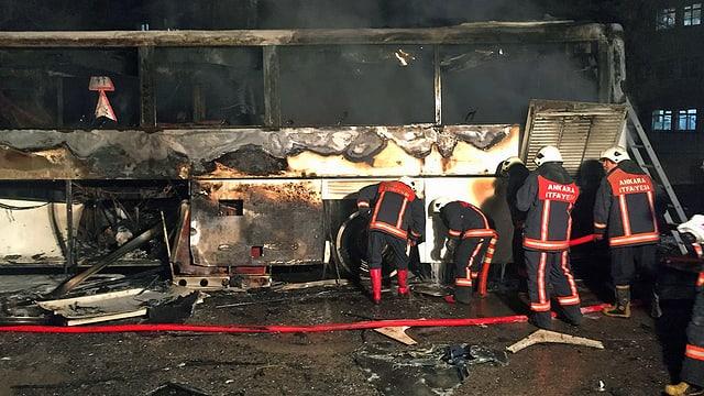 Feuerwehrmänner und ausgebrannter Bus.