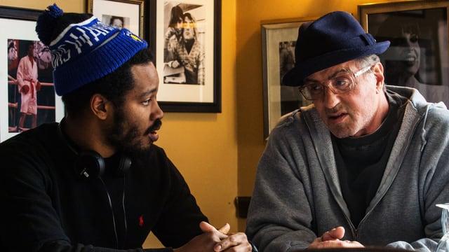 Sylvester Stallone und Ryan Coogler sitzen an einem Tisch.