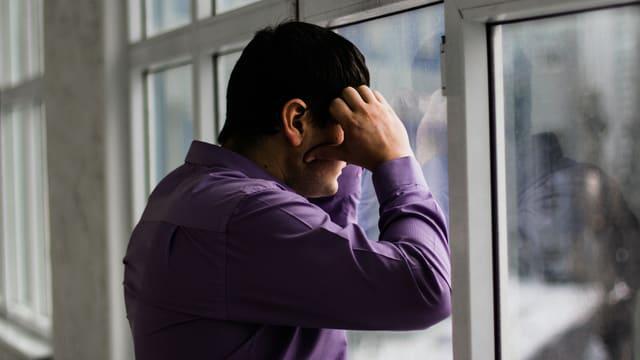 Mann stützt sich an Fenster.