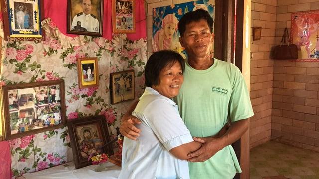 Ein Mann und eine Frau im Innern eines Hauses, Fotos schmücken die Wand.