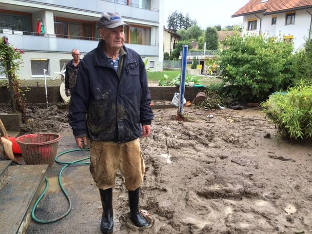Ein älterer Mann steht in seinem Garten voller Schlamm.