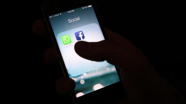 Persuna che tegn in telefonin che mussa duas apps da social media.