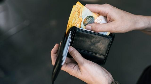 Eine Hand nimmt zwei 10-Franken-Scheine aus einem Portemonnaie.