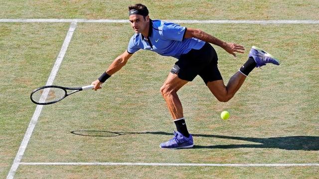 Federer en acziun e curra per la balla da tennis.