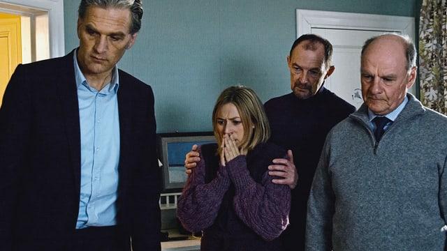 Drei Männer und eine Frau blicken sichtbar schockiert zu Boden.