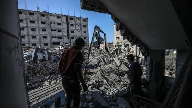 Zwei Männer neben zertrümmerten Häusern