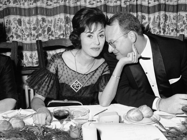 Ein Ehepaar an einem gedeckten Tisch.