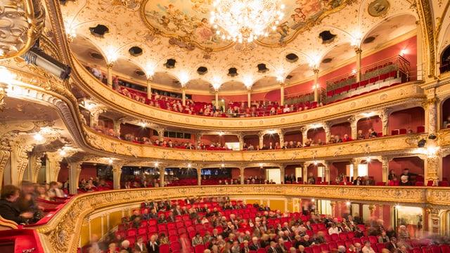Blick ins innere des Opernhaus Zürich. Zuschauerränge sind zur Hälfte gefüllt.