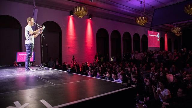 Ein Mann leist auf einer Bühne von einem Zettel