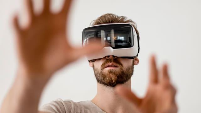 Ein Mann mit einer VR Brille tastet suchend mit seinen Händen durch die Luft.