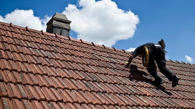 Kaminfeger auf einem Dach.