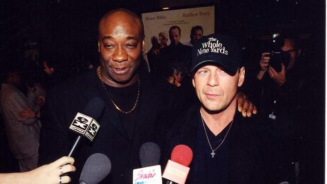 Zwei Männer stehen nebeneinander, ihnen werden fünf Mikrofone vors Gesicht gehalten. Im Hintergrund ein Filmplakat, auf dem die beiden Männer und zwei weitere abgebildet sind.