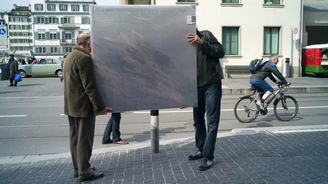 Zwei Männer tragen ein verhülltes Gemälde über eine Strasse.