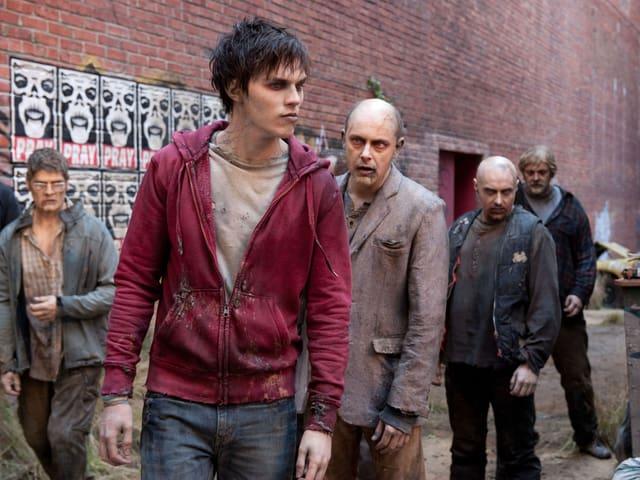 Eine Gruppe von Zombies läuft durch eine Strasse.