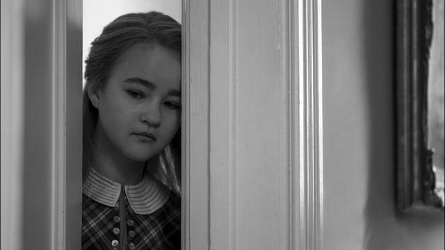 Ein Mädchen schaut durch eine halboffene Türe.
