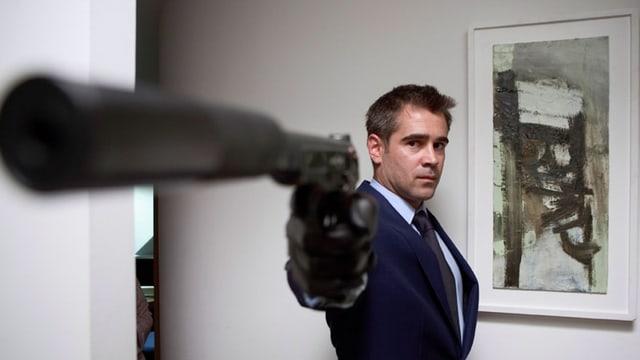 Ein Mann richtet die Waffe auf ein unbekanntes Ziel.