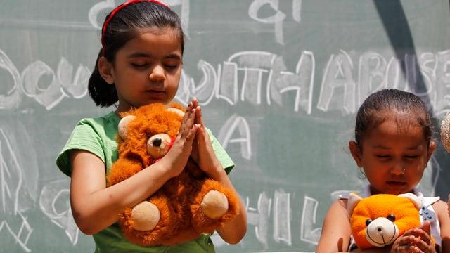 Mädchen betend mit einem Teddy-Bären.
