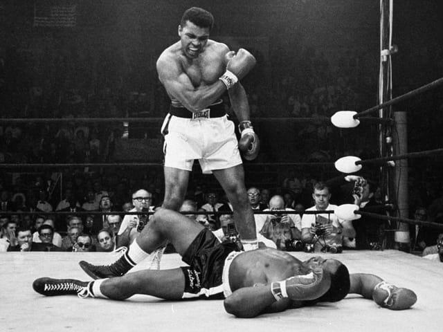 Ein Boxer hat seinen Gegner k. o. geschlagen und schaut auf ihn runter.