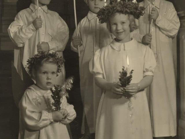 Ein schwarz-weiss Bild von Prinzessin Anne-Marie und Margrethe. Sie sind damals noch kleine Kinder, tragen beide ein weisses Kleid und halten eine Kerze in der Hand.